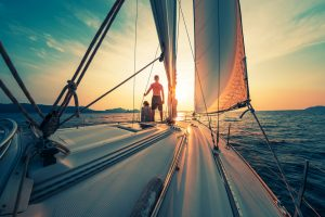 Young,Couple,Sailing,On,The,Boat,At,Sunset